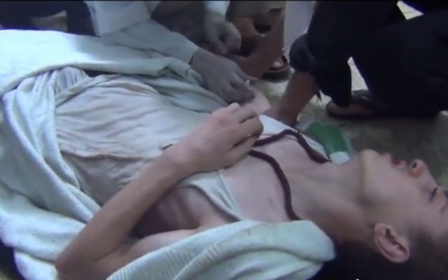 A man suffering a siezure, from a video reporting to show victims of the chemical attack outside Damascus Wednesday. (Screenshot: YouTube)