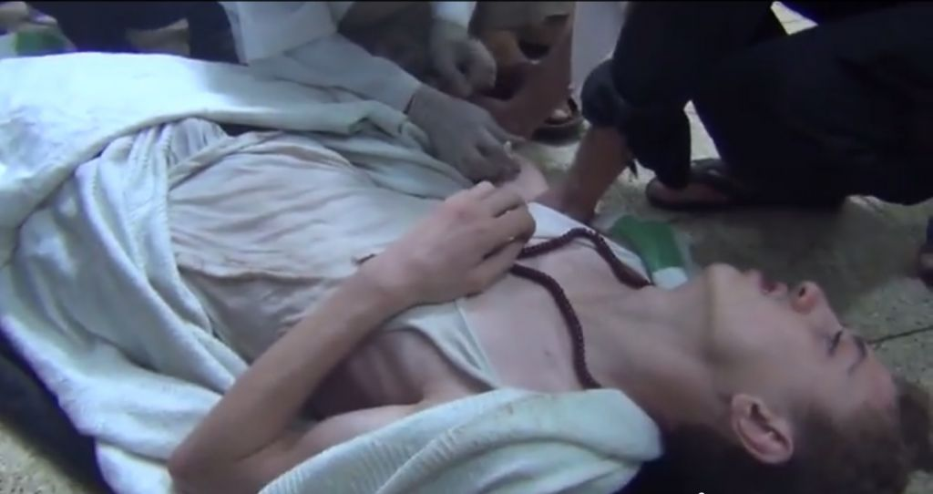 A man suffering a seizure, from a video reporting to show victims of the chemical attack outside Damascus Wednesday. (Screenshot: YouTube)