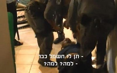 Image of Boaz Albert getting arrested by police. The subtitles read 'Give him the electricity already' and 'Why? Why?' (photo credit: YouTube screen capture)