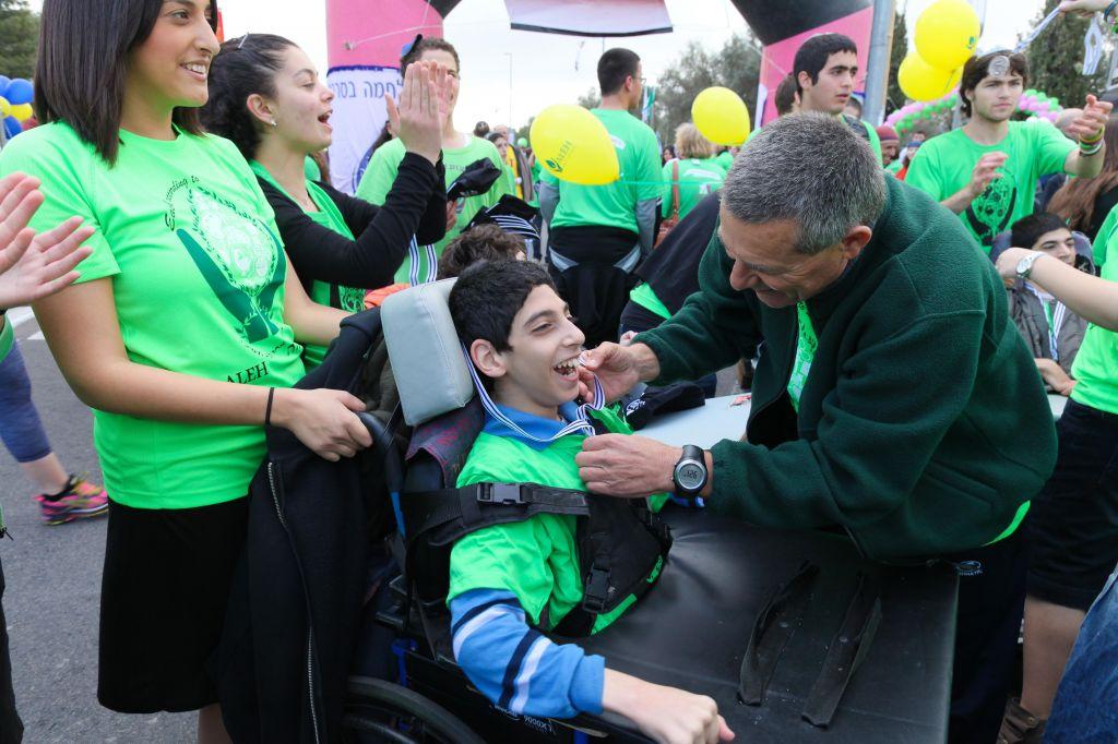Doron Almog puts a medal on a child from ALEH Jerusalem child at the Jerusalem Marathon. (photo credit: courtesy Aleh)