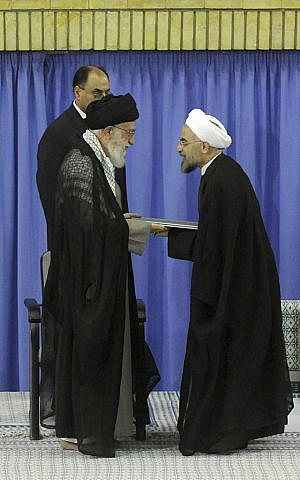In this picture released by the official website of the Iranian supreme leader's office, Supreme Leader Ayatollah Ali Khamenei, left, gives his official seal of approval to President-elect Hasan Rouhani, in an official endorsement ceremony, in Tehran, Iran, Saturday, Aug. 3, 2013. (photo credit: AP Photo/Office of the Iranian Supreme Leader)