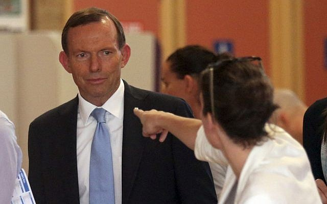 A woman points at Australia's opposition leader Tony Abbott while he waits to cast his vote at Freshwater Surf Life Saving Club polling station in Sydney, Australia, Saturday, Sept. 7, 2013. (photo credit: AP/Rob Griffith)