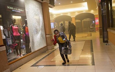 A woman who had been hiding during the gun battle runs for cover after armed police, seen behind, enter the Westgate Mall in Nairobi, Kenya, Saturday, Sept. 21, 2013. Gunmen threw grenades and opened fire Saturday, killing at least 22 people in an attack targeting non-Muslims at an upscale mall in Kenya's capital that was hosting a children's day event, a Red Cross official and witnesses said. (AP Photo/Jonathan Kalan)