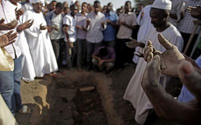 Sudanese men pray over the body of Salah Sanhory, 26, who was killed on Friday Sept. 27, 2013 by security forces, during his funeral in Khartoum, Sudan, Saturday, Sept. 28, 2013. (photo credit: AP/Khalil Hamra)
