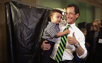 Democratic mayoral hopeful Anthony Weiner holds his son Jordan as he leaves the voting booth after casting his vote at his polling station during the primary election in New York, Tuesday, Sept. 10, 2013. (photo credit: AP Photo/Mary Altaffer)