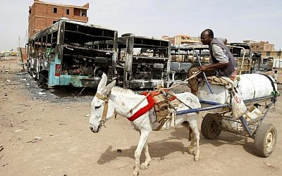 A man on a donkey cart passes burned buses following rioting and unrest in Khartoum, Sudan, Thursday, September 26, 2013. Sudanese authorities have deployed troops around vital installations and gas stations in Khartoum following days of deadly rioting over gas price hikes. (photo credit: AP Photo/Abd Raouf)