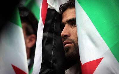 A Syrian immigrant who lives in Bulgaria observes a minute of silence during a demonstration in front of the European Commission Representation office in Sofia, Bulgaria, Saturday, Aug. 31, 2013 (photo credit: AP/Valentina Petrova)