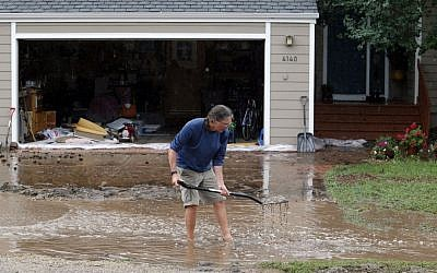 A man clears a drains in front of a house in Boulder, Colorado, on Thursday (photo credit: AP/Ed Andrieski)