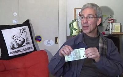 Annals of Improbable Research editor Eric Abrahams shows off this year's new cash prize. (photo credit: YouTube screenshot)