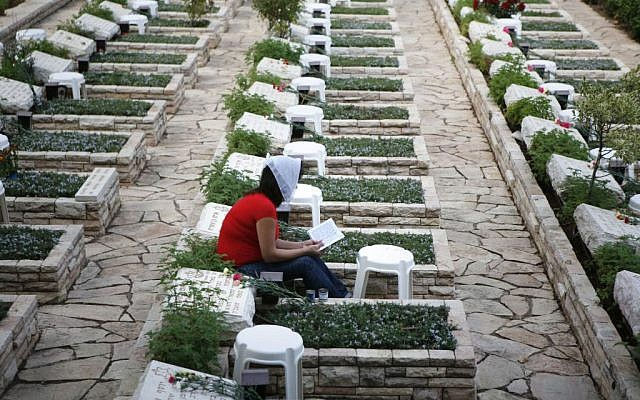 A  woman sits next to the grave of fallen soldier from the 1973 Yom Kippur War, in the Mount Herzl military cemetery in Jerusalem (Michal Fattal/Flash90)