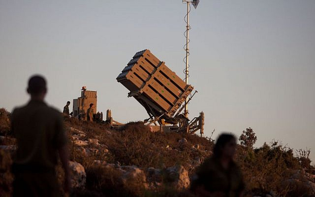 Israeli soldiers walk by an Iron Dome missile defense system deployed near Jerusalem, September 2013. (photo credit Flash90)