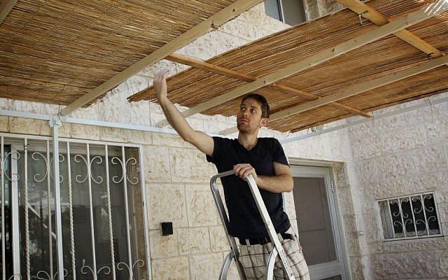 Illustrative photo of a young man building a sukkah. (Gershon Elinson/Flash90)