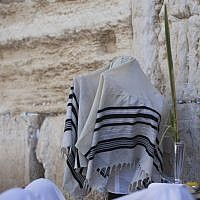 A religious Jew of the priestly caste spreads his prayer shawl over his head as he takes part in a mass prayer in front of the Western Wall in Jerusalem, Sunday, September 22, 2013 (photo credit: Yonatan Sindel/Flash90)