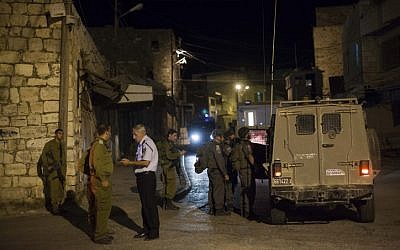 Israeli soldiers stand near the scene of a shooting in the city of Hebron on September 22, 2013 (photo credit: Yonatan Sindel/Flash90)