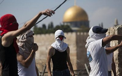 Palestinians hurl stones at Israeli police officers (unseen) in East Jerusalem (photo credit: Yonatan Sindel/Flash90)