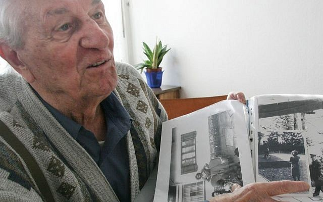 In this March 10, 2005 file photo Hitler's bodyguard Rochus Misch points to a picture of Adolf Hitler he had taken in Berchtesgarden, southern Germany, in the early 1940th in his house in Berlin. Misch, who was the last remaining witness to the Nazi leader's final hours in his Berlin bunker, died Thursday, Sept. 5, 2013. He was 96. (AP Photo/Herbert Knosowski, File)