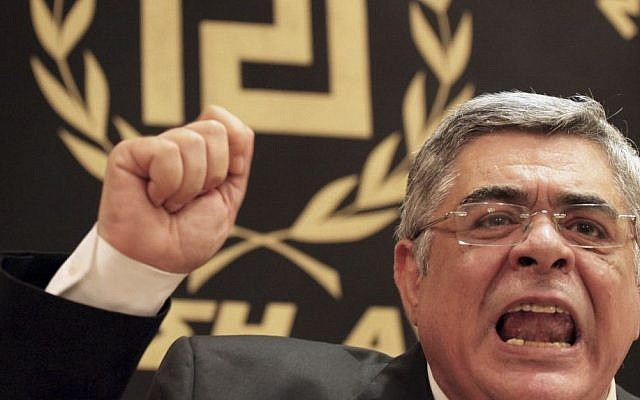 In this May 6, 2012 file photo, Golden Dawn party leader Nikos Michaloliakos speaks during a news conference in front of a banner with the twisting Maeander, an ancient Greek decorative motif that the party has adopted as its symbol, in Athens. (AP/Petros Giannakourism, File)