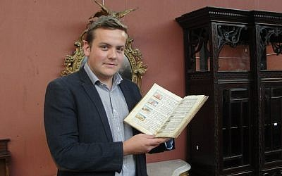 Forrest holding the 'Manchester Garage Haggadah' (photo credit: courtesy)