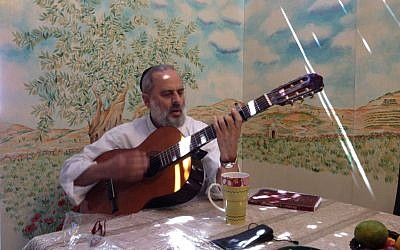 Shimon Matthews strums his guitar to a tune he composed for Sukkot, against the recently completed mural in his sukkah (photo credit: Jessica Steinberg/Times of Israel)