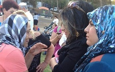 Jewish Kurdish women from Israel and Muslim Kurdish women from Iraq converse in Sorani Kurdish after meeting each other at the 2013 Saharane festival in Jerusalem (photo credit: Times of Israel/ Lazar Berman)