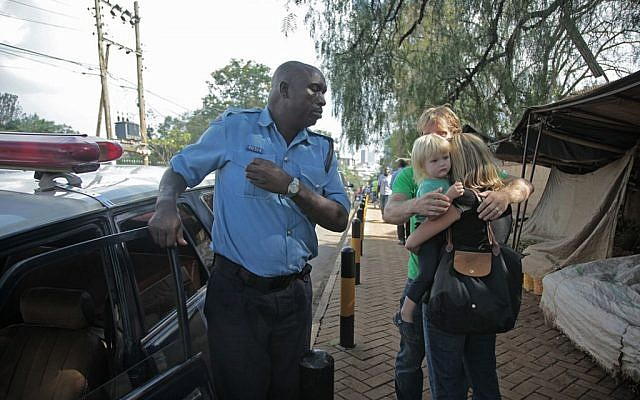 Lyndsay, centre right, embraces daughter Julia and husband Nick, partially seen, in a reunion that came after the couple had been separated for three hours inside a mall under attack by al-Shabab terrorists in Nairobi, Kenya on Saturday, Sept. 21, 2013. The couple, friends of an AP reporter, were texting and calling the AP reporter during the hostage crisis, blurring the lines between journalist and friend. (photo credit: AP/Georgina Goodwin)