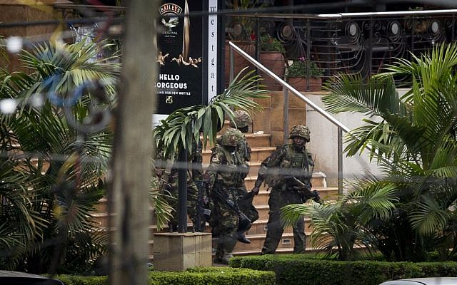 Soldiers from the Kenya Defense Forces carry a wounded colleague, following the sound of explosions and gunfire, out of the Westgate Mall in Nairobi, Kenya, on Sunday, September 22, 2013 (photo credit: AP/Ben Curtis)