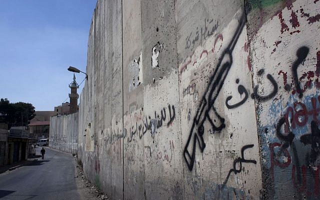 """A Palestinian man walks by the barrier separating the West Bank town of Abu Dis from East Jerusalem. The Arabic graffiti, seen on the Abu Dis side, reads, """"PLO, no for negotiations."""" Monday, September 9, 2013. (photo credit: AP/Nasser Nasser)"""