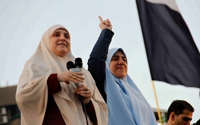 Naglaa Mahmoud, left, the wife of Egypt's ousted president Mohammed Morsi, alongside her daughter, addresses thousands of Morsi supporters gathered at a sit-in in Cairo's Nasr City, in August (photo credit: AP/Ravy Shaker/El Shorouk Newspaper/File)