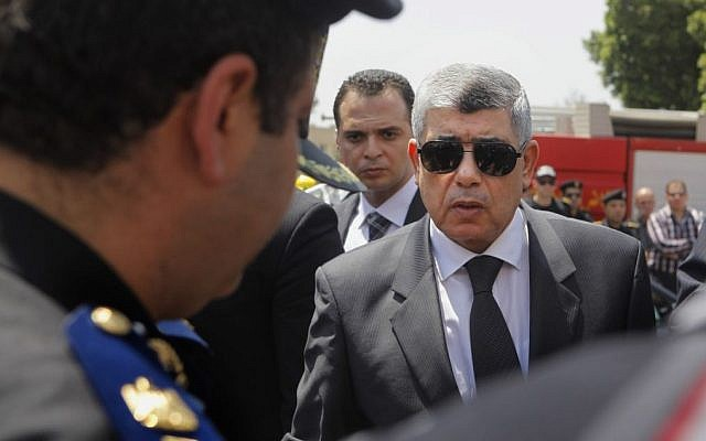 In this Thursday, Aug. 15, 2013, file photo, Egyptian Interior Minister Mohammed Ibrahim, right, gives his condolences to a policeman during a military funeral in Cairo, Egypt. (Photo credit: AP/Amr Nabil, File)