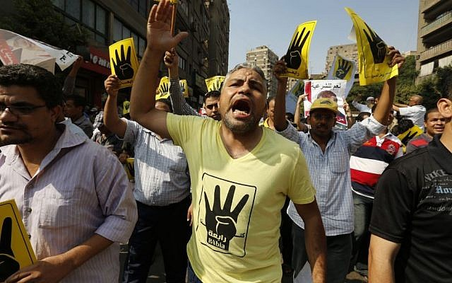 A supporter of the Muslim Brotherhood wears a shirt with the pro-MB symbol, during a march in Cairo, Egypt, on September 6, 2013 (photo credit: AP/Lefteris Pitarakis)