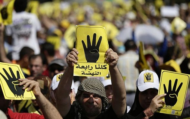 Supporters of Egypt's ousted president Mohammed Morsi chant slogans and hold placards showing an open palm with four raised fingers, which has become a symbol of the Rabaah al-Adawiya mosque, where Morsi supporters held a sit-in for weeks, in Cairo on Friday (photo credit: AP/Hassan Ammar)