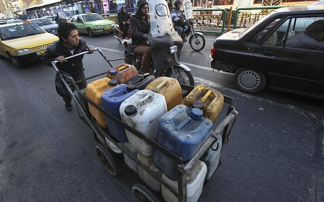 Illustrative photo of an Iranian pushing a cart loaded with fuel containers at the Enqelab-e-Eslami (Islamic Revolution) street in Tehran, Iran. (AP Photo/Vahid Salemi, File)