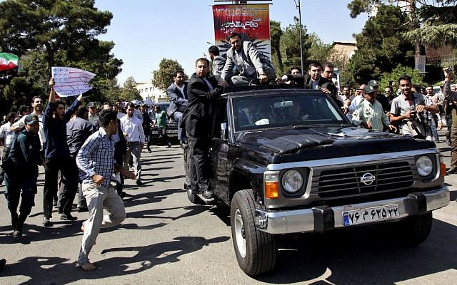 A protester, left, approaches President Hasan Rouhani's car leaving Mehrabad airport after his arrival from the U.S. in Tehran, Iran, Saturday, Sept. 28, 2013.(photo credit: AP Photo/Ebrahim Noroozi)
