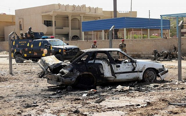 Officers of Police Quick Reaction Force inspect the site of a car bomb attack in front of their headquarters in the town of Suwayrah, 25 miles (40 kilometers) south of Baghdad, Iraq, on Sunday, September 15, 2013. (photo credit: AP/Hadi Mizban)