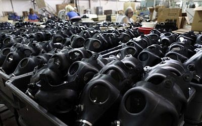 Workers are seen at the Shalon gas mask factory in Kiryat Gat, Israel, in August 2013 (photo credit: AP/Tsafrir Abayov)