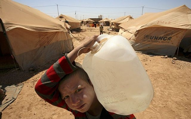 A Syrian boy carries a water jug to his family's tent at the Zaatari Refugee Camp, in Mafraq, Jordan (photo credit: AP/Mohammad Hannon/File)