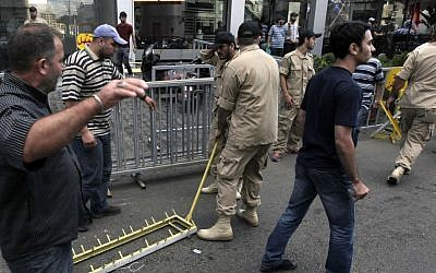 Members of Lebanon's Hezbollah group remove one of their checkpoints in a southern suburb of Beirut, Lebanon, Monday, Sept. 23, 2013. (Photo credit: AP/Bilal Hussein)