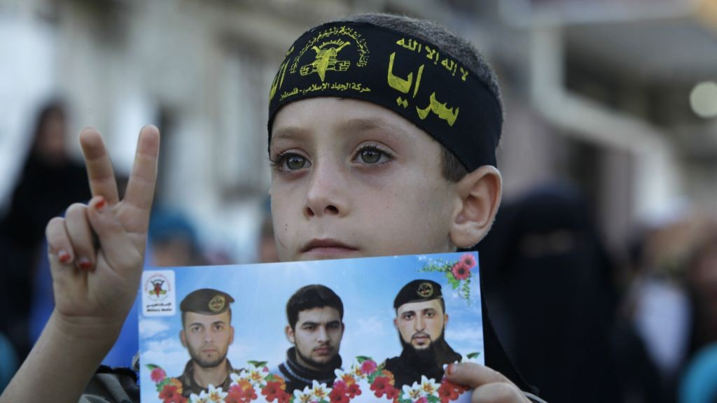 A young supporter of Islamic Jihad holds a picture of group members killed in clashes with Israeli forces, during a rally marking the 13th anniversary of the Second Intifada, in the Jabaliya Refugee Camp, northern Gaza Strip, on Thursday (photo credit: AP/Adel Hana)