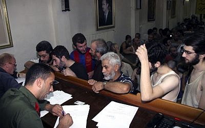 In this file photo, Syrian prisoners sign their papers of release at the Damascus Police Command headquarters in Damascus, Syria, on September 1, 2012. (photo credit: AP/Bassem Tellawi)