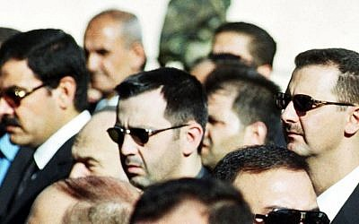 In this June 13, 2000 file photo, Syrian President Bashar Assad, right, his brother Maher, center, and brother-in-law Major General Assef Shawkat, left, stand during the funeral of late president Hafez Assad in Damascus, Syria (photo credit: AP)