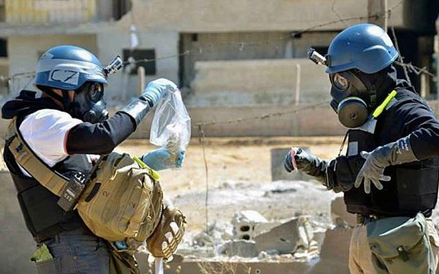 Illustrative image of members of a UN investigative team taking samples near the site of an alleged chemical weapons attack, in Syria, August 28, 2013. (AP/United Media Office of Arbeen)