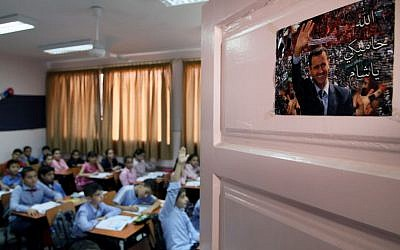 "In this Wednesday, Sept. 18, 2013 photo, Syrian pupils attend class at Hassan Shuaib School in Damascus, Syria. A poster on the door depicting President Bashar Assad in Arabic reads,""God is protecting you, Syria."" (AP Photo)"