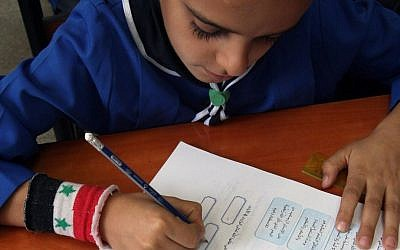 In this Wednesday, Sept. 18, 2013 photo, a Syrian boy writes in his workbook during a lesson at Hassan Shuaib School in Damascus, Syria. (AP Photo)