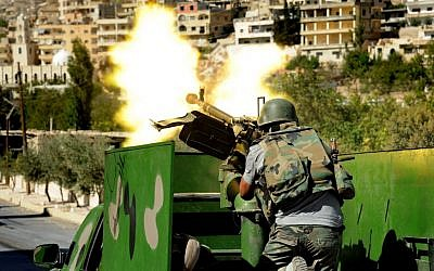 A Syrian solider fires a heavy machine gun during clashes with rebels in Maaloula village, northeast of the capital Damascus in 2013. (photo credit: AP/SANA)