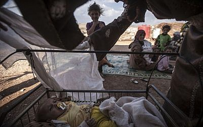 In this Sunday, September 22, 2013 photo, a Syrian internally displaced mother comforts her baby at an abandoned area where she and her family have taken shelter after fleeing their village that turned into a battlefield between government forces and Free Syrian Army fighters in Idlib province, northern Syria. (AP Photo)