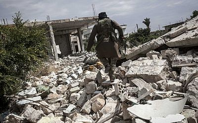 A Free Syrian Army fighter walks among rubble of a home destroyed by a warplane bomb in the Idlib province on September 22, 2013. (photo credit:AP)