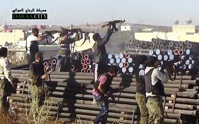 In this image taken from Wednesday, Sept. 25, 2013, video obtained from the Sham News Network, Syrian opposition fighters fire at government forces near Daraa customs in Daraa al-Balad, Syria. (Photo credit:AP/Sham News Network via AP video)