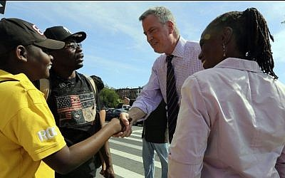Democratic mayoral hopeful Bill de Blasio, center, and wife Chirlane McCray, right greet supporters after a campaign rally in the Brooklyn borough of New York, Sept. 7, 2013. (photo credit: AP Photo/Mary Altaffer)