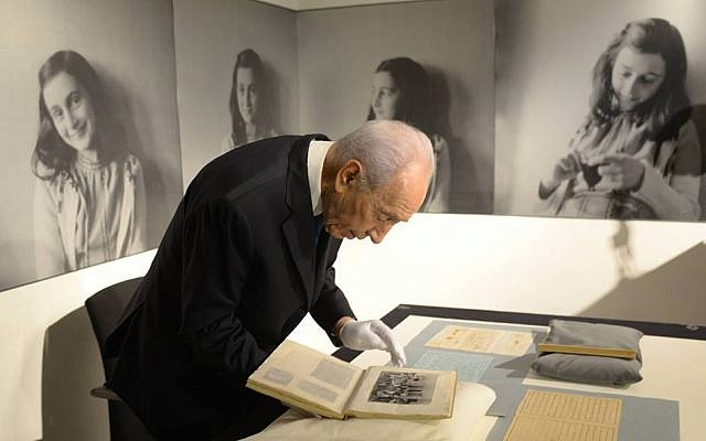 President Shimon Peres reviews original segments from the diary of Anne Frank during a visit to Amsterdam, September 30, 2013. (photo credit: Facebook/Shimon Peres)