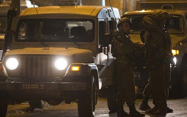 IDF soldiers stand near a shooting scene in the city of Hebron on September 22, 2013 (photo credit: Yonatan Sindel/Flash90)